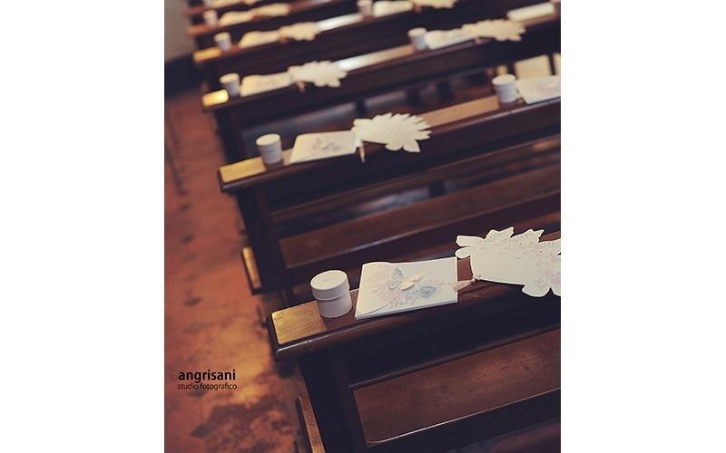 banchi di una chiesa addobbati per matrimonio