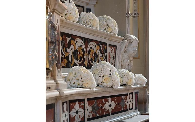altare di una chiesa con addobbi floreali