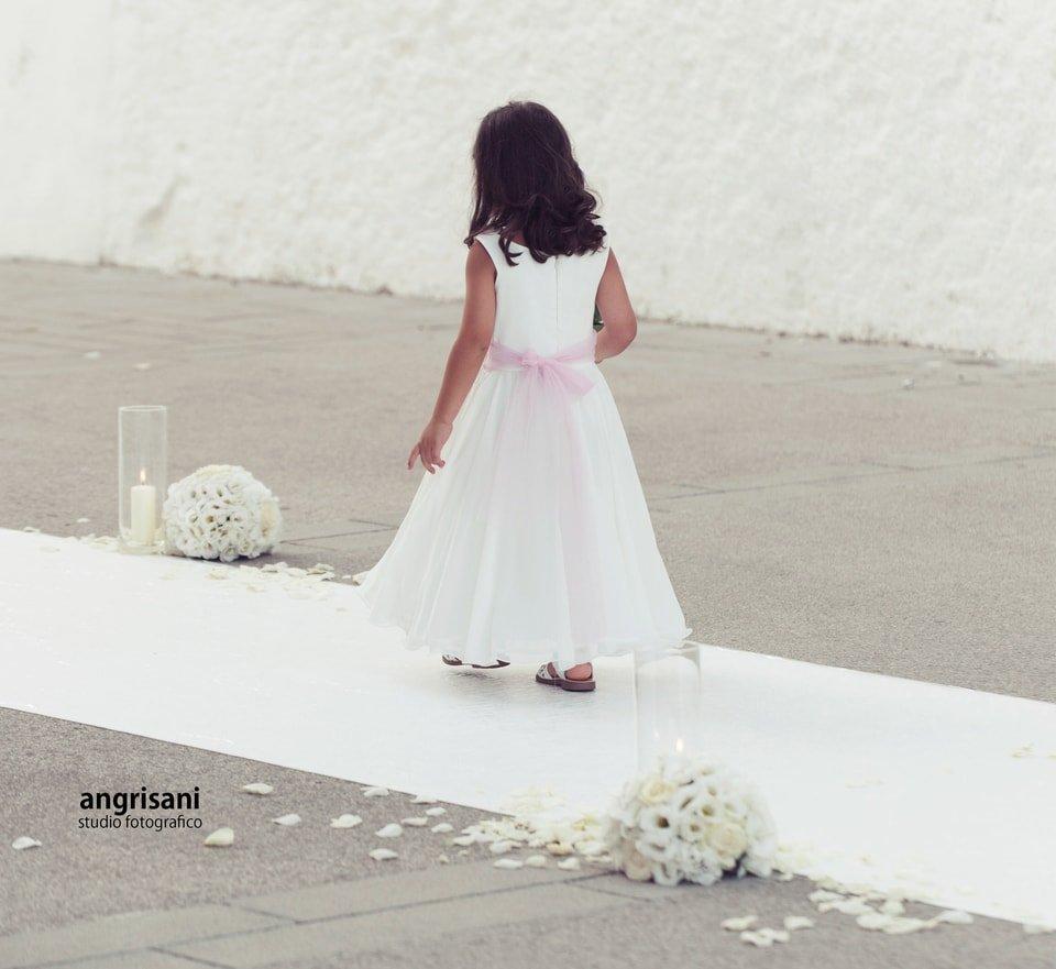 bambina di bianco vestita con bouque bianchi sulla strada