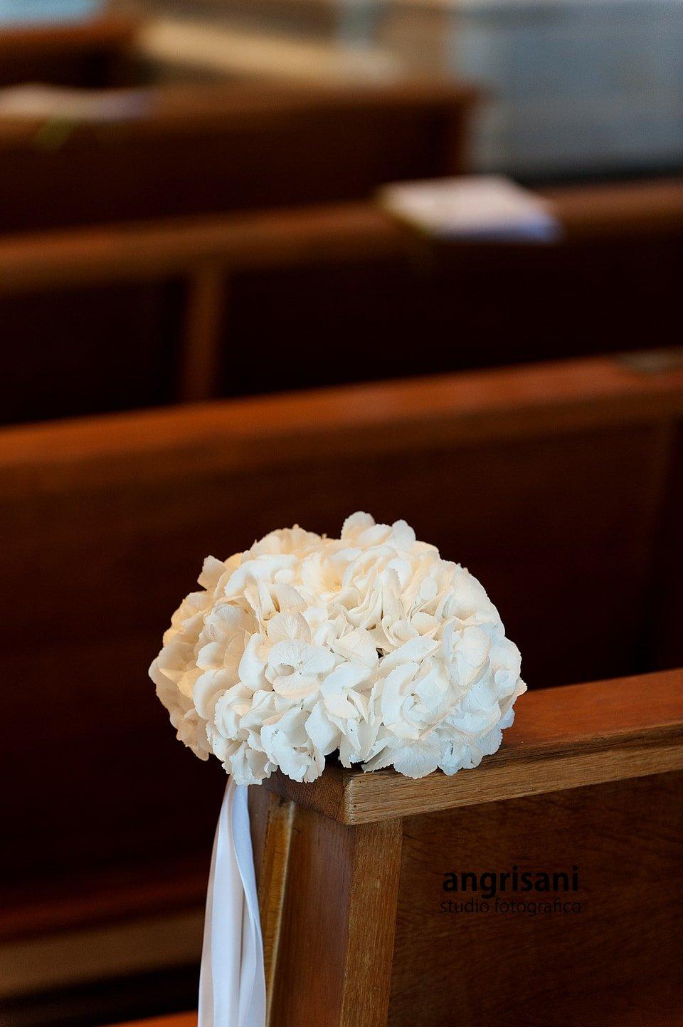 bouquet bianco su un banco di una chiesa