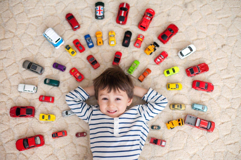 un bambino sdraiato in mezzo a delle macchine giocattolo