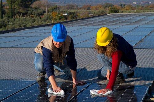 addetti mentre  puliscono un impianto fotovoltaico