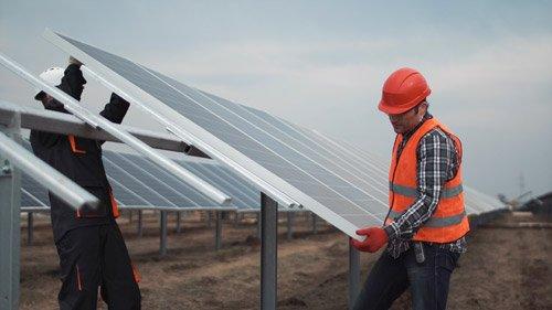 addetti mentre sollevano un impianto fotovoltaico