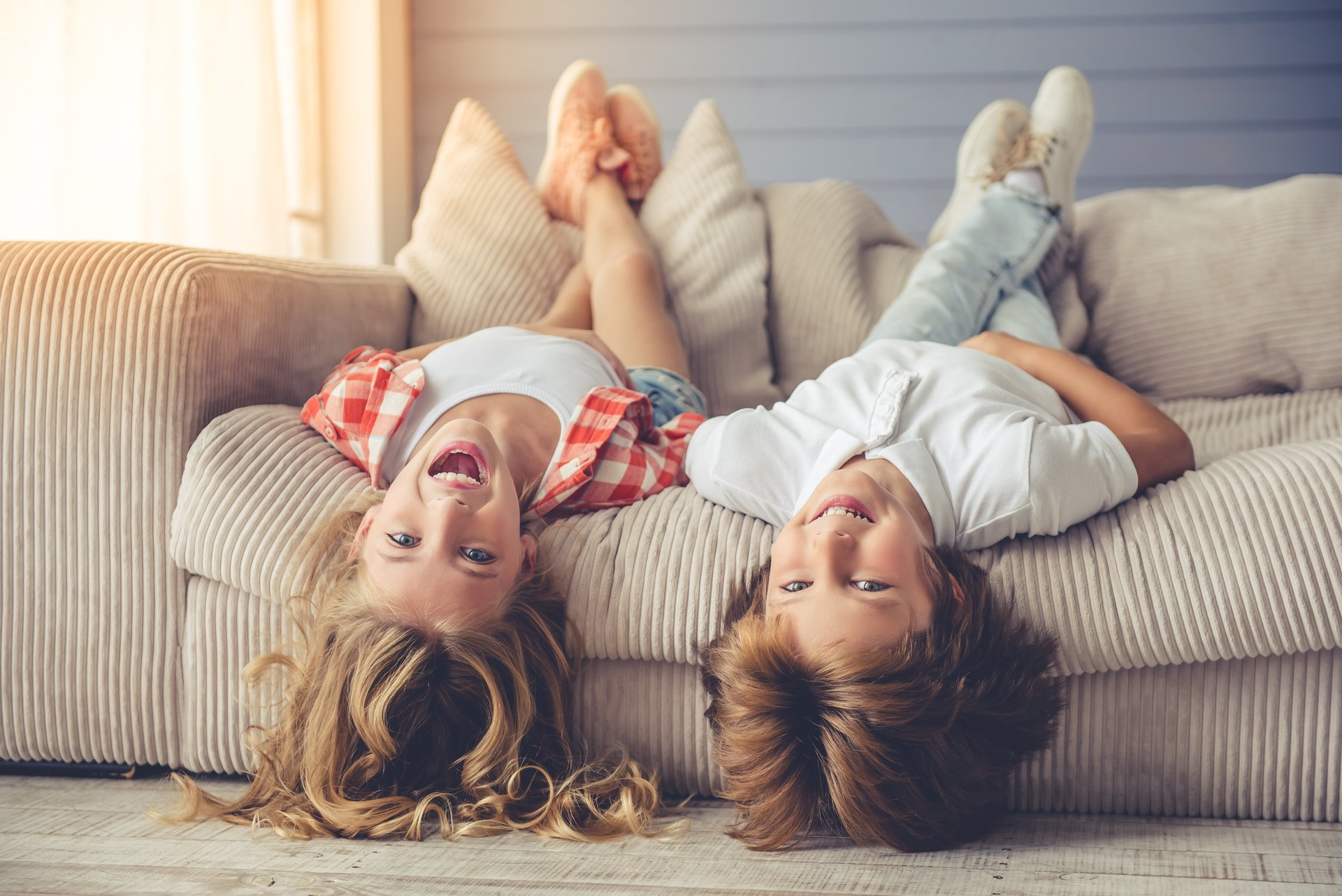A girl and boy lying upside down on the couch