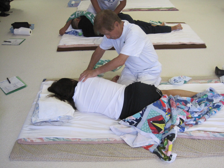 A man demonstrating a Shiatsu massage on an arm