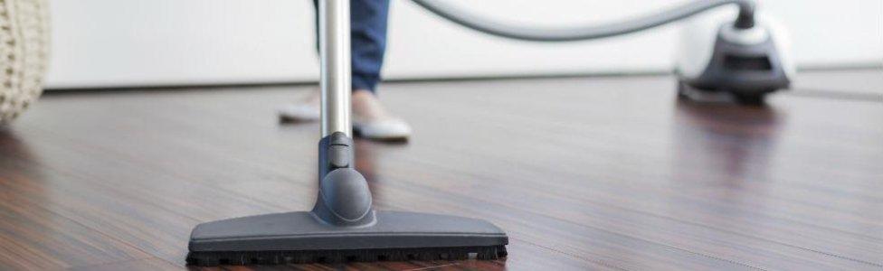 aspirapolvere mentre pulisce pavimento di casa