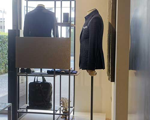 delle giacche e una borsa su un piccolo scaffale