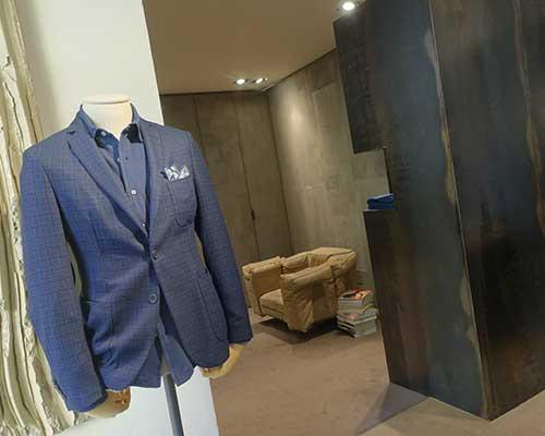 una giacca blu appesa su un manichino