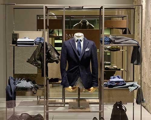 una giacca blu con una cravatta appesa su un manichino e altro