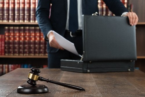 Midsection of lawyer putting documents
