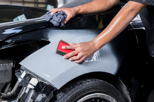 operaio mentre pulisce una macchina con mani