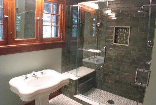interno di un bagno con un lavabo bianco, sopra una finestra in legno e sulla destra la vetrata di un box doccia