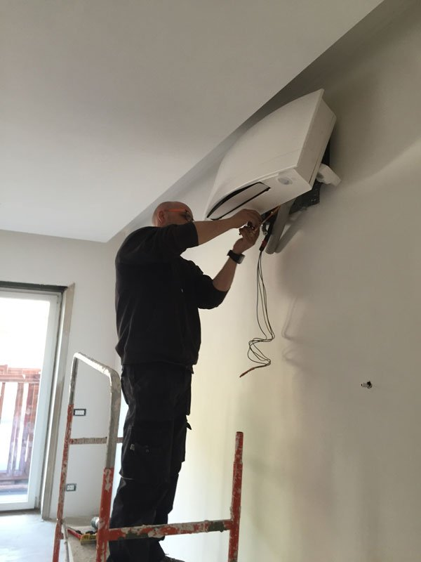 un uomo sta installando un condizionatore di color bianco al muro