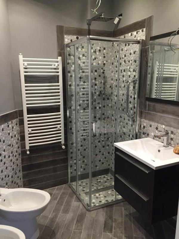 un bagno moderno con sulla sinistra il wc, di fronte un porta asciugamani bianco a muro, un box doccia con piastrelle a mosaico bianche e nere e sulla destra un lavabo con sotto un mobiletto