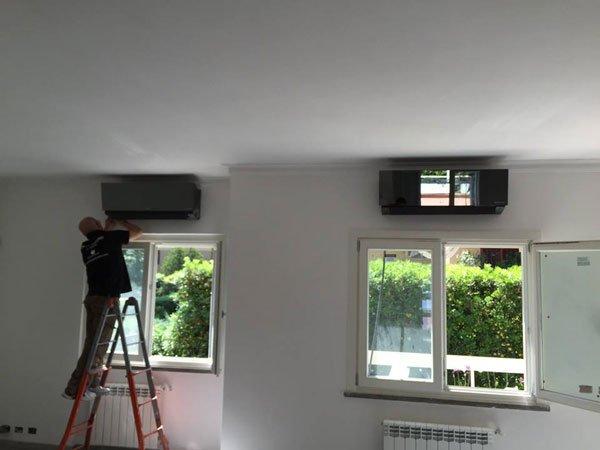 vista di due finestre di cui una  aperta e davanti un uomo sulla scala che sta posizionando un condizionatore sul muro