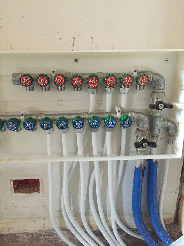 un impianto idrico con diversi rubinetti con manopole rotonde rosse e blu con tubi in gomma attaccati e tubature in ferro
