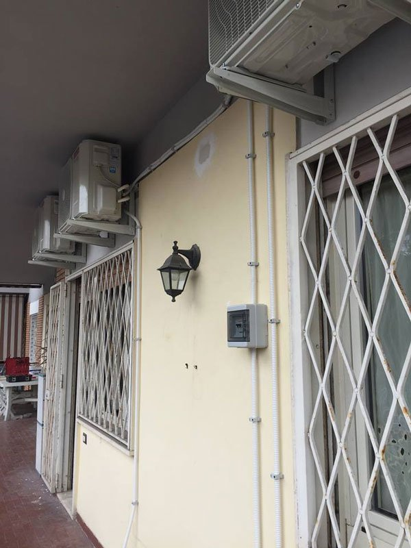 vista laterale dell'esterno di uno stabile con porte con inferiate a griglia bianche e sopra ogni porta un motore da condizionatore