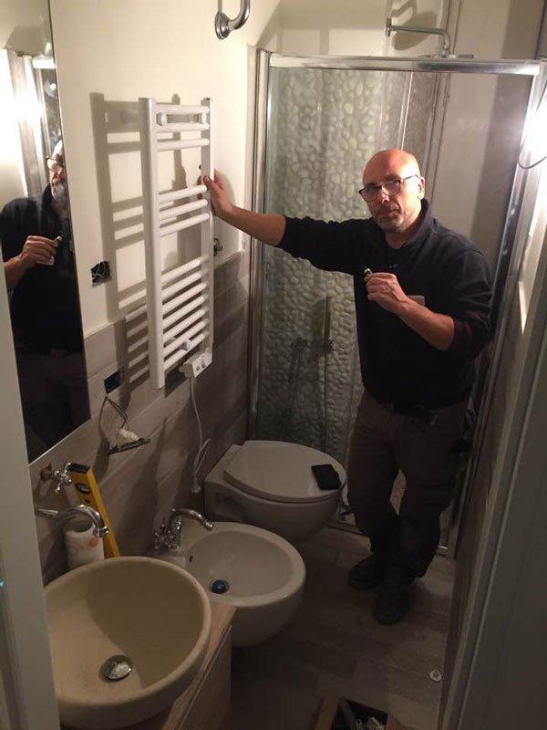 un bagno con sulla sinistra lavabo,bidet, wc, un uomo in piedi appoggiato su un porta asciugamani a muro e dietro un box doccia