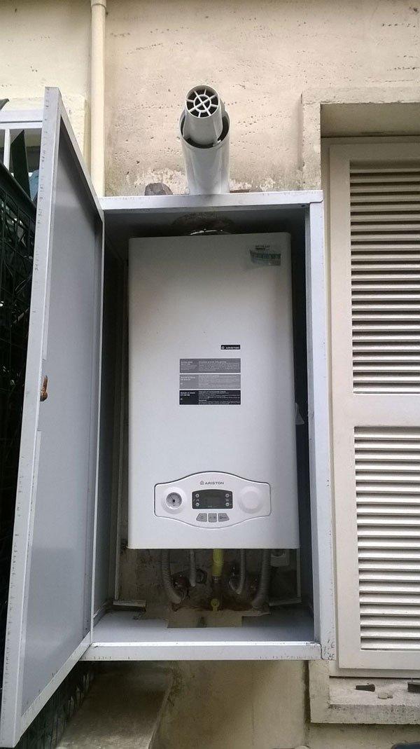 un armadio di metallo aperto e all'interno una caldaia di color bianco