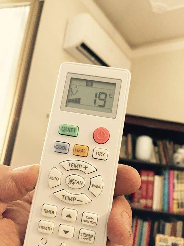-una mano che impugna un telecomando di un condizionatore che segna 19 gradi visto da vicino