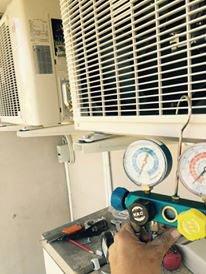 vista di un manometro appeso con un gancio alla griglia di un motore di un condizionatore