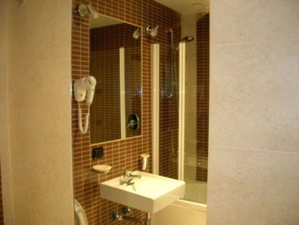 un lavabo di un bagno con sopra uno specchio, un fon bianco appeso al muro, il tutto su uno sfondo di piastrelle arancioni