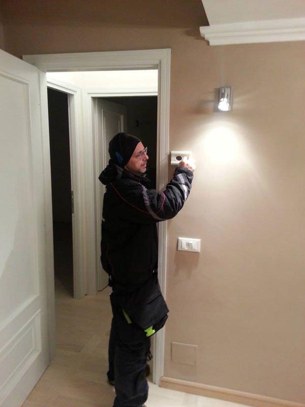 un uomo con un cappellino di lana e un' uniforme da lavoro nera mentre sta facendo delle foto in un appartamento