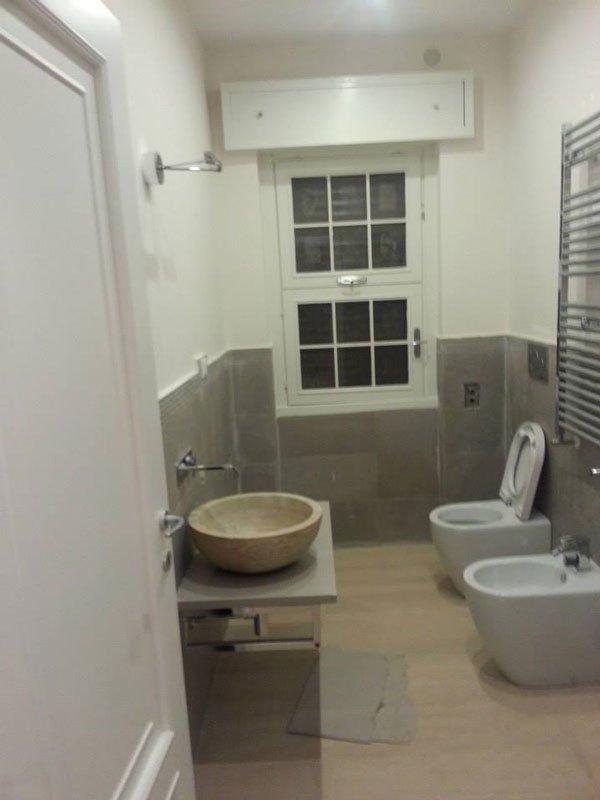 bagno con bidet e wc sulla destra di fronte un rubinetto installato nel  muro e sotto un lavabo beige a forma circolare sorretto da una lastra di marmo