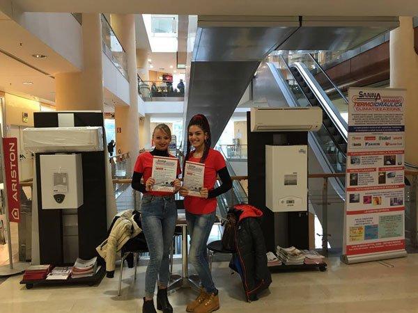 ue ragazze, una bionda e una mora con delle brochure in mano all'interno di un centro commerciale per promuovere la marca Ariston