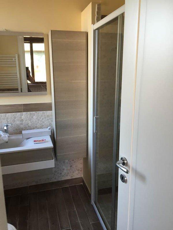 interno di un bagno con di fronte un lavabo, sulla destra una porta in vetro e accanto un' altra porta bianca con una maniglia in acciaio