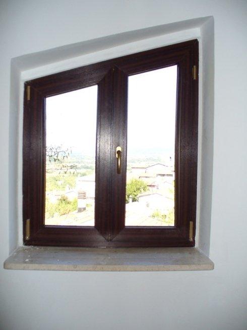 Finestra in PVC effetto Mogano a trapezio con maniglia bronzo