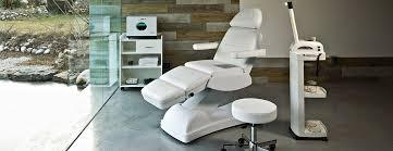 Una stanza con un lettino reclinabile, carrello e uno sgabello di color bianco