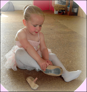 young girl weaing a tutu sitting down putting on ballet shoes