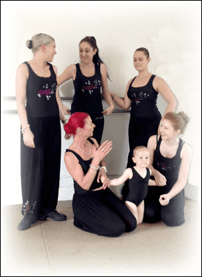 woman, girls and a children in a dance studio against a white wall