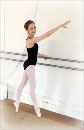 girl in a leotard performing ballet postitions whilst holding on to a bar