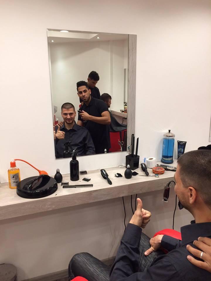 cliente e parrucchiere davanti allo specchio in posa per una foto