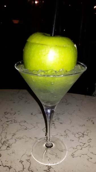 composizione di un cocktail con una mela intera e cannuccia inserita dentro