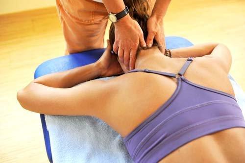 fisioterapista massaggia il collo a una paziente