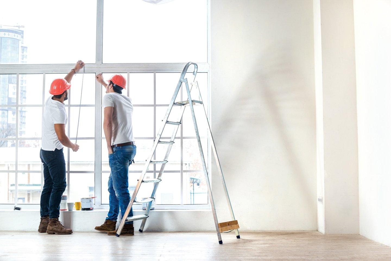 Due operai prendono le misure di una porta finestra