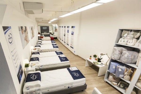 una donna sdraiata su un letto in uno showroom