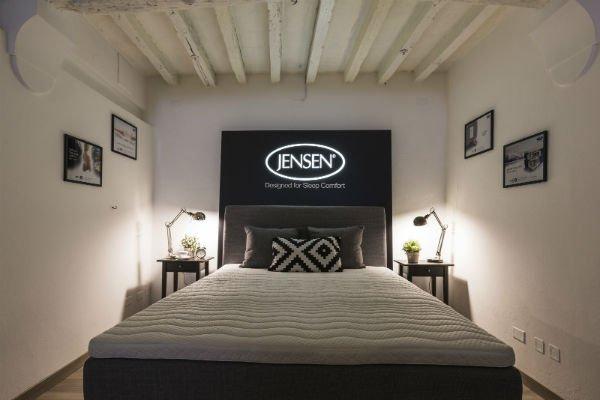 un letto matrimoniale di color grigio con un materasso e dei cusini