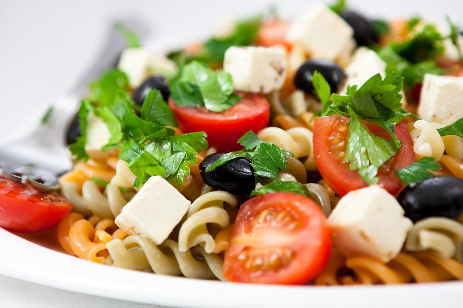 Un'insalata di pasta La vetrina di una rosticceria con dei piatti pronti