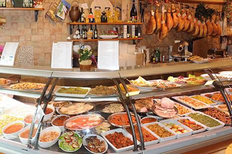 La vetrina della rosticceria con piatti pronti e dietro dei salumi appesi