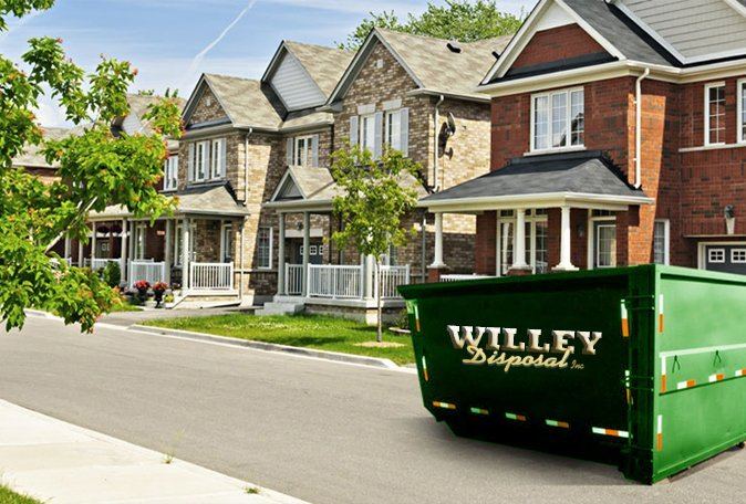 A neighborhood with a Willey Disposal dumpster in the street
