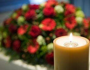 una candela in primo piano e fiori nello sfondo.