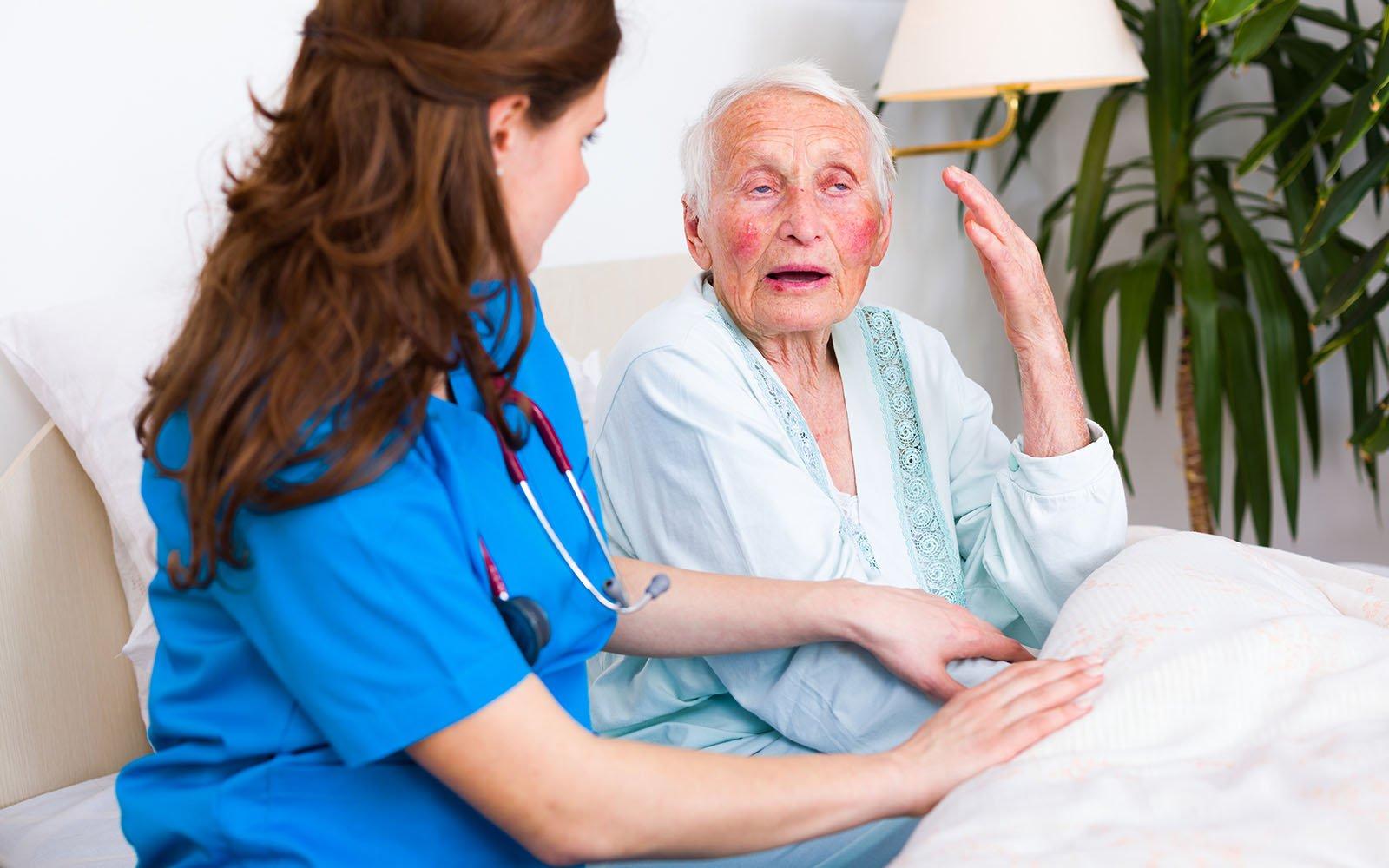 un'infermiera accanto a un uomo anziano che parla