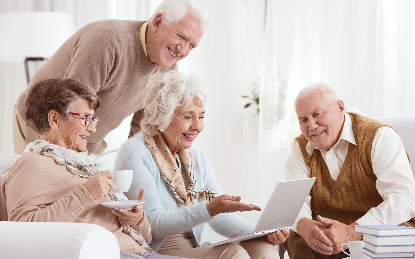una signora anziana che usa il computer e altri che guardano sorridendo