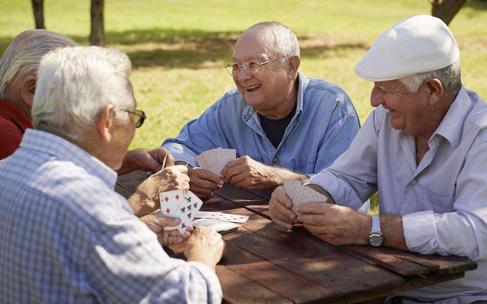 dei signori anziani seduti a un tavolo all'aperto mentre giocano a carte