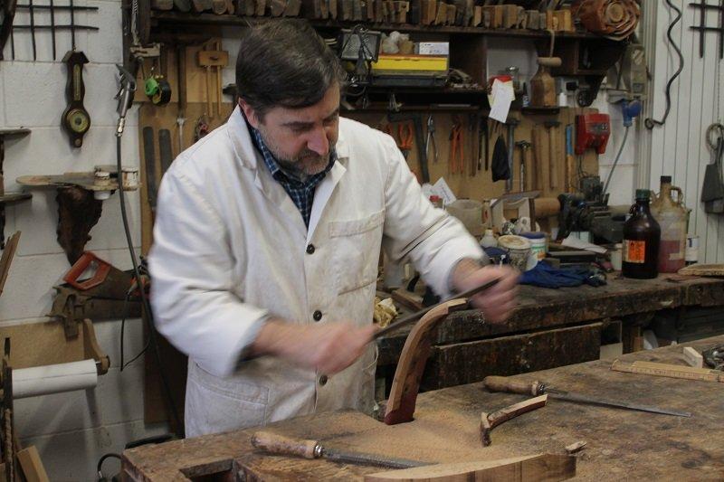 titolare con camice bainco che restaura un articolo di legno