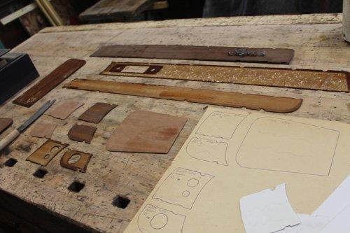 pezzi di legno da restaurare appoggiati su una superficie da lavoro